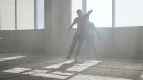 2 друз успешных танцоров танцуют breakdance в получившемся отказ пылевоздушном здании Тренируя умелые тазобедренные hopers акции видеоматериалы