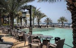 Дубай Небесный оазис в Рас-Аль-Хайма Пляж с sunbeds и навесами в Дубай, на берегах аравийского залива тонизировать Стоковые Фотографии RF