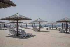 Дубай Небесный оазис в Рас-Аль-Хайма Пляж с sunbeds и навесами в Дубай, на берегах аравийского залива тонизировать Стоковое Фото