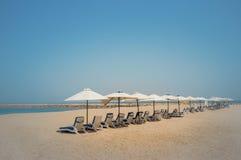 Дубай Небесный оазис в Рас-Аль-Хайма Пляж с sunbeds и навесами в Дубай, на берегах аравийского залива тонизировать Стоковая Фотография