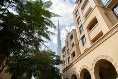 ДУБАЙ, ОАЭ - 13-ОЕ НОЯБРЯ 2018: Башня Burj Khalifa и al Souk жилые дома городка Bahar старые на сценарной предпосылке небес с стоковое изображение