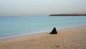 Дубай, ОАЭ - 21-ое января 2018: Сиротливое арабское wooman на пляже наблюдая на море на восходе солнца акции видеоматериалы