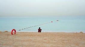 Дубай, ОАЭ - 21-ое января 2018: Сиротливый арабский человек на пляже наблюдая на море на восходе солнца акции видеоматериалы