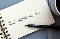 ДУМАЙТЕ ВНЕ КОРОБКИ рук-lettered в блокноте с ручкой щетки стоковые изображения