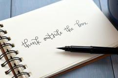 ДУМАЙТЕ ВНЕ КОРОБКИ рук-lettered в блокноте Стоковое Изображение RF
