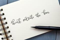 ДУМАЙТЕ ВНЕ КОРОБКИ рук-lettered в блокноте стоковая фотография