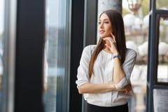 Думать бизнес-леди, standinding около окна в ресторане стоковое фото rf