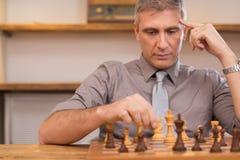 Думая бизнесмен играя шахмат Стоковые Фотографии RF