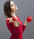 Думая девушка офиса 20s держа тупые колоколы для тонизированных оружий и здоровья Стоковая Фотография