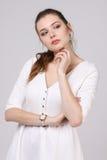 Думая женщина в белом платье стоя на серой предпосылке стоковая фотография