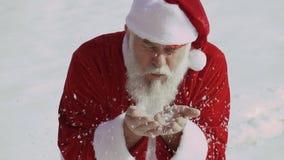 Дуновение Санта Клауса с снежинок от его рук сток-видео