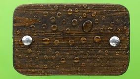 Дуновения ветра на дождевых каплях на темной деревянной доске с болтами утюга Изолировано на зеленой предпосылке сток-видео