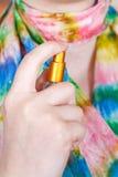 Дух девушки распыляя на silk шарфе от атомизатора Стоковые Фото