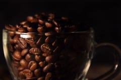Душистые зажаренные в духовке кофейные зерна коричневеют и придают форму чашки стоковое фото rf