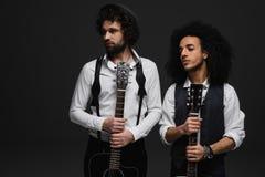 дуэт красивых молодых музыкантов с акустическими гитарами смотря прочь стоковое фото rf