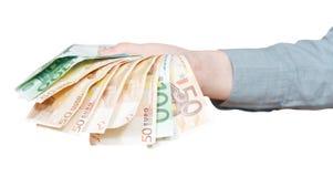 Дуют банкноты евро в изолированной руке Стоковое Изображение