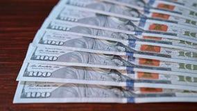 Дуют куча 100 банкнот доллара на таблице Стоковые Фотографии RF