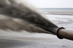 Дуя песок сделал инженерство земли морем Стоковые Изображения RF