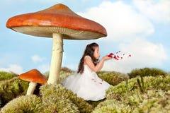 дуя fairy лепестки девушки подняли Стоковое Изображение