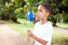 дуя pinwheel мальчика Стоковое Изображение