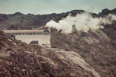 Дым от печной трубы фабрики в горах Стоковая Фотография
