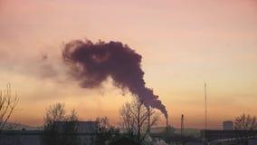 Дым от труб боилеров и домов в зиме против неба захода солнца, трассировок самолетов летания в небе видеоматериал