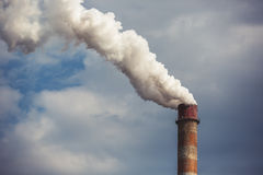 Дым поднимая от промышленной печной трубы Стоковое Изображение