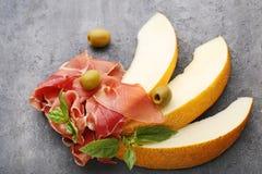 Дыни с jamon, листьями базилика и оливками Стоковые Изображения