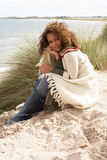дюны зашкурят сидя детенышей женщины Стоковое Фото