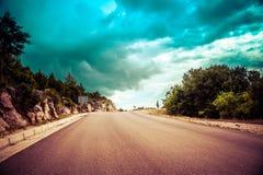 Длинная бесконечная дорога в сельской местности без движения с облаками Стоковое Фото