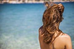 Длинная белокурая красная девушка волос наблюдая на море с рукой над h Стоковая Фотография RF