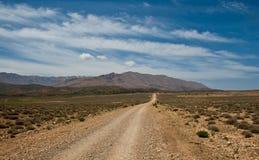 Длинная грязная улица водит к горам Стоковая Фотография