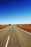 Длинное простирание шоссе через австралийское захолустье Стоковая Фотография