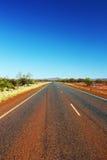Длинное простирание шоссе через австралийское захолустье Стоковые Изображения RF