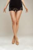 Длинные, ровные ботинки лакированной кожи девушек ног Стоковые Фото