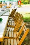 Длинные таблицы в строке сада деревянных стульев Подготовка для внешней травы фестиваля пикника или публики лета зеленой, солнечн Стоковое Изображение
