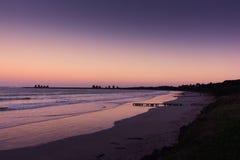 Длинный песчаный пляж на заходе солнца с фиолетовыми небесами и водой Стоковая Фотография