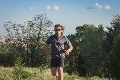 Длинный с волосами спортсмен бежать в парке города стоковое изображение rf