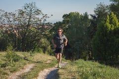 Длинный с волосами спортсмен бежать в парке города стоковое фото