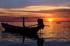 Длинн-замкнутая шлюпка и заход солнца Стоковые Изображения