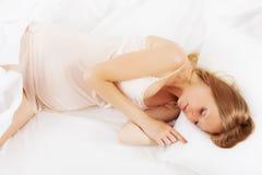 Длинн-с волосами беременная женщина спать на белой подушке стоковые изображения rf