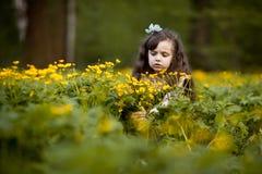 Длинн-с волосами девушка с желтыми цветками Стоковые Изображения