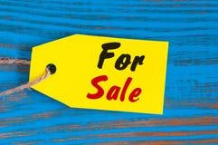 Для продажи бирка на голубой деревянной предпосылке Продажи, скидка, реклама, одежды ценников маркетинга, меблировкы, автомобили Стоковое Изображение
