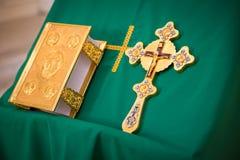 Евангелие в золотой рамке и золотой крест на зеленой ткани на стойке Стоковая Фотография