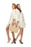 2 девочка-подростка в белых пальто с сумкой Стоковое Изображение