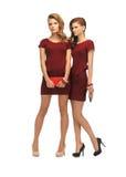 2 девочка-подростка в красных платьях с муфтами Стоковые Фотографии RF