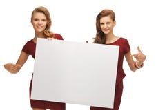2 девочка-подростка в красных платьях с пустой доской Стоковое фото RF