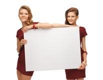 2 девочка-подростка в красных платьях с пустой доской Стоковые Фото