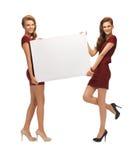 2 девочка-подростка в красных платьях с пустой доской Стоковая Фотография