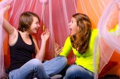 2 девочка-подростка имея потеху на кровати Стоковые Фото